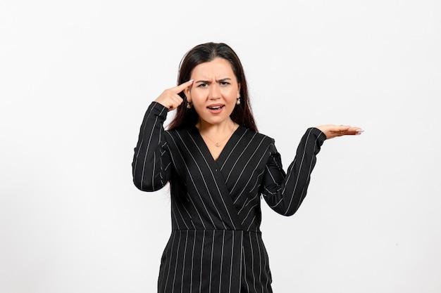 Impiegato femminile in abito nero rigoroso in posa su bianco chiaro