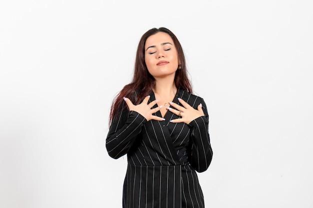 Impiegato femminile in abito nero rigoroso in posa su bianco