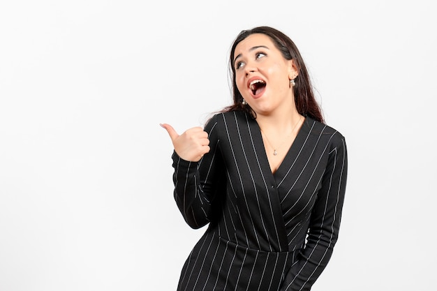 Female office employee in strict black suit posing on white