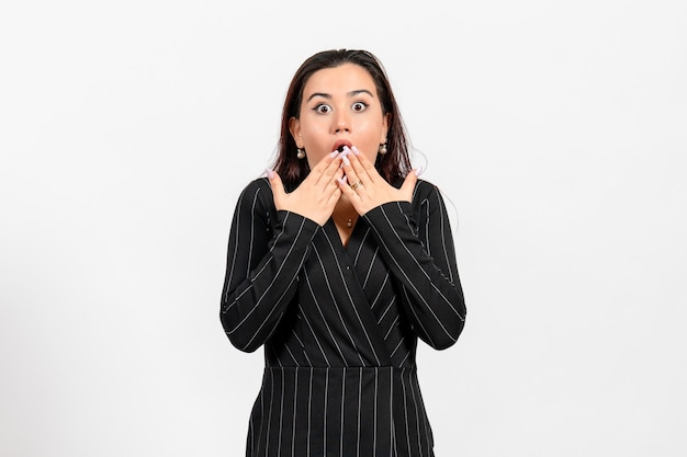 Female office employee in strict black suit posing with shocked face on white