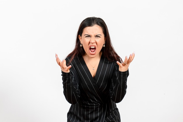 Female office employee in strict black suit screaming on white