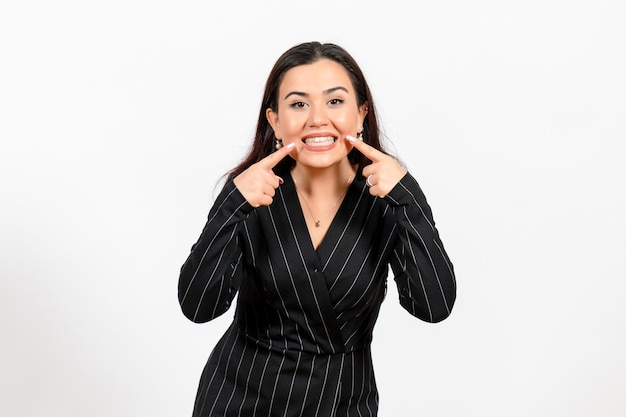 Female office employee in strict black suit showing her teeth on white
