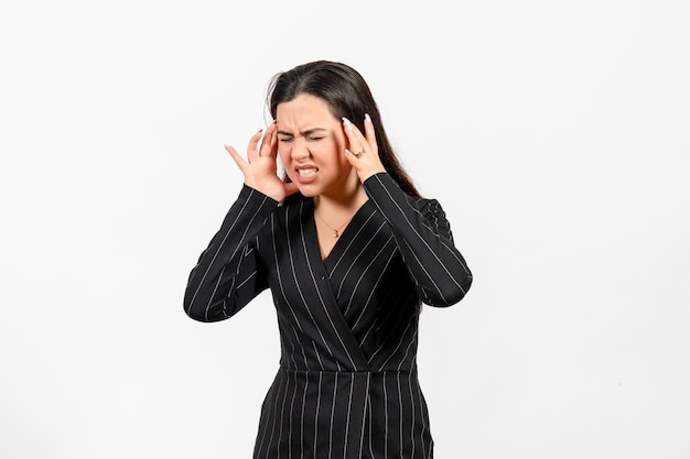 Female office employee in strict black suit suffering from headache on white
