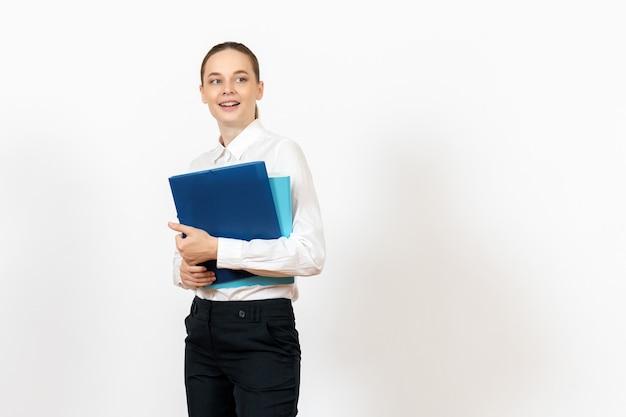 Impiegato femminile di ufficio in camicetta bianca che tiene i documenti su bianco