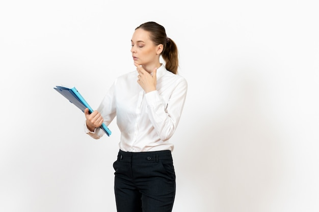 Female office employee in white blouse holding documents on white