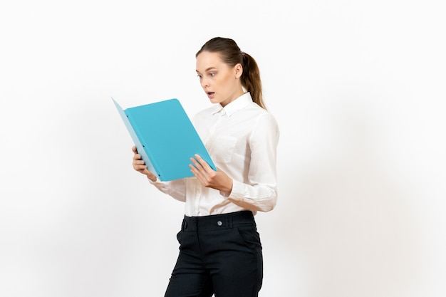 Female office employee in white blouse holding and reading blue file on light-white