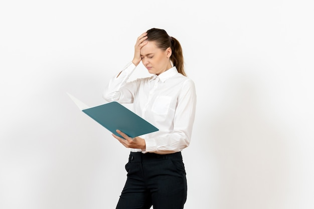 Female office employee in white blouse holding and reading blue file on white