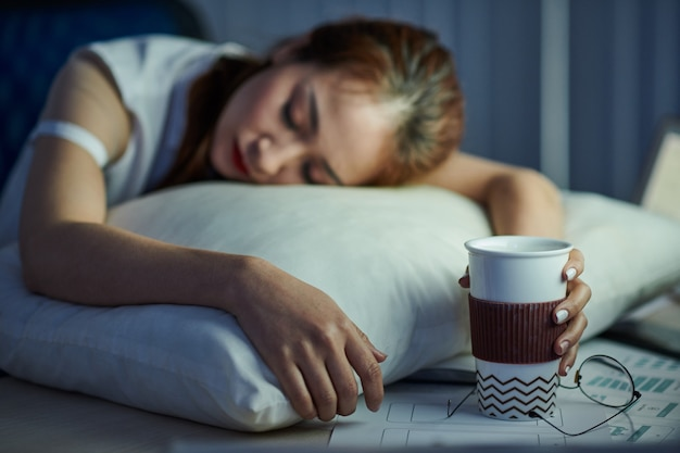 女性サラリーマンがコーヒーカップを手に持ち帰り、机で眠りについた
