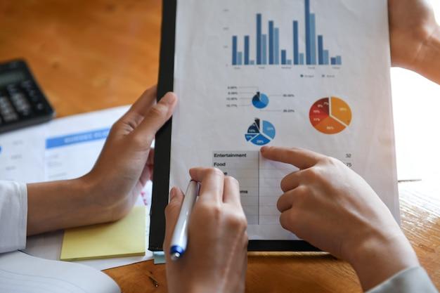 Женский офисный работник, проведение диаграммы данных. они указывают на графики для анализа данных.