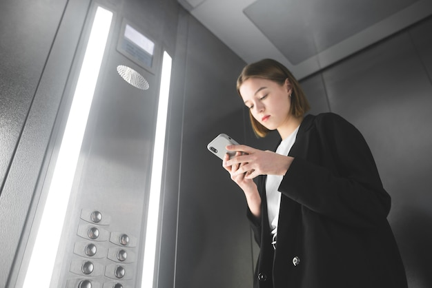 Female office worker is looking at her smartphone screen in the elevator.