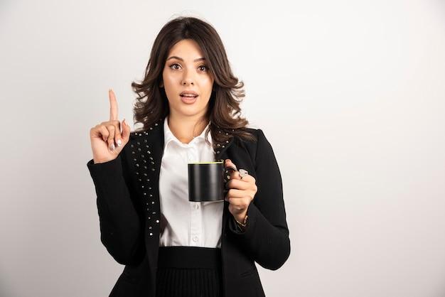 お茶を飲みながら逆さまを指す女性サラリーマン