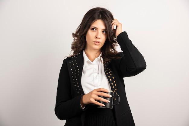 Impiegata femminile in posa con una tazza di tè