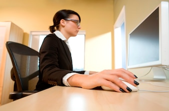 Female office worker sitting at a computer and holding a computer mouse