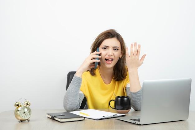 Женский офисный работник сидит за столом и разговаривает по мобильному телефону.