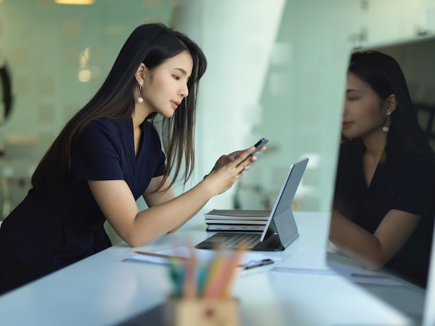 Female office worker using smartphone while working in office room