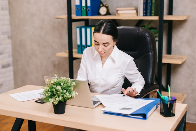 職場でドキュメントを表示する女性サラリーマン Premium写真