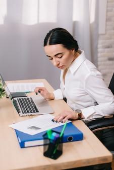 職場でドキュメントを表示する女性サラリーマン