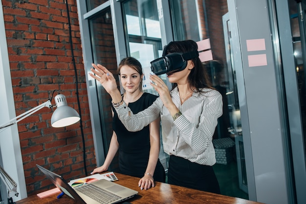 Female office workers having fun at work watching 3d video in vr goggles.
