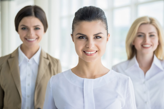 Female office workers standing in line and smiling