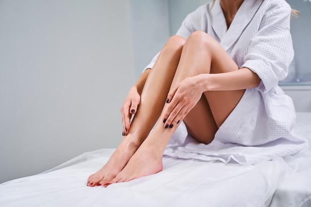 소파에 앉은 여성이 미용사에서 제모 절차를 마친 후 다리를 만지고 부드러움을 즐기고 있다