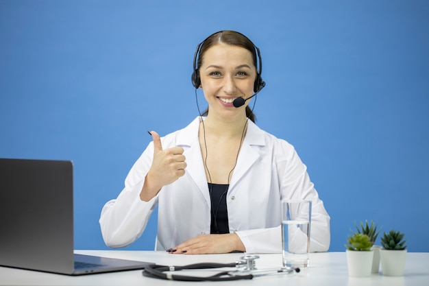 Female online consultant in white coat and headset smiling and showing like sign