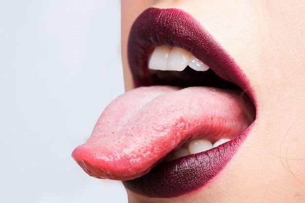Женский открытый рот с сексуальными губами, фиолетовая помада и язык