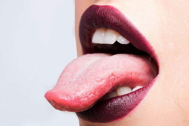 Female open mouth with sexy lips purple lipstick and tongue