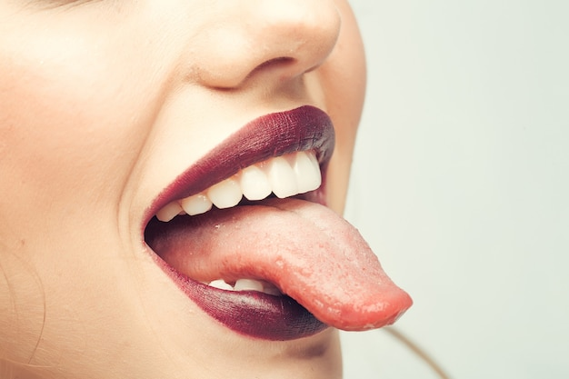 Female open smiling mouth with sexy lips purple lipstick and tongue