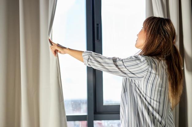 朝起きた後、パジャマ姿でカーテンを開ける女性