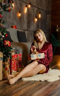女性は魔法のクリスマスプレゼントを開きます。プレゼントを開く若い女性