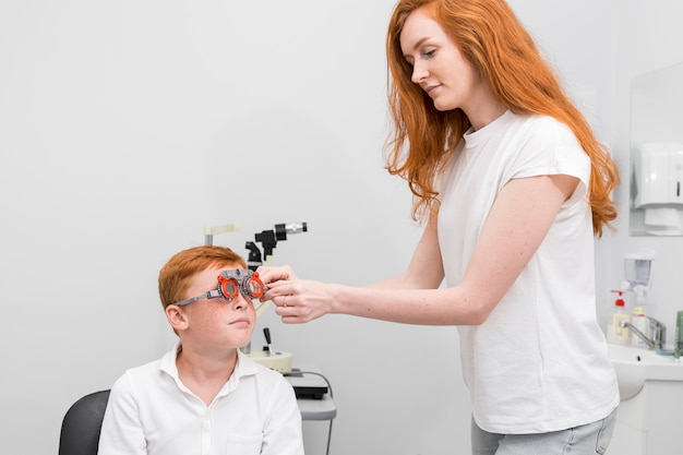 Female ophthalmologist examining boy eyes with optometrist trial frame