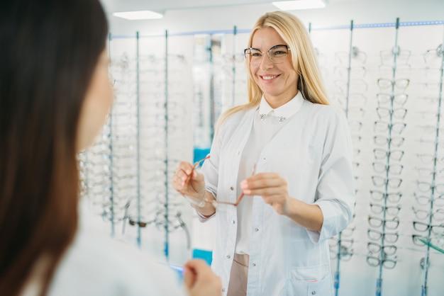 Женский оптик и покупательница снимает очки