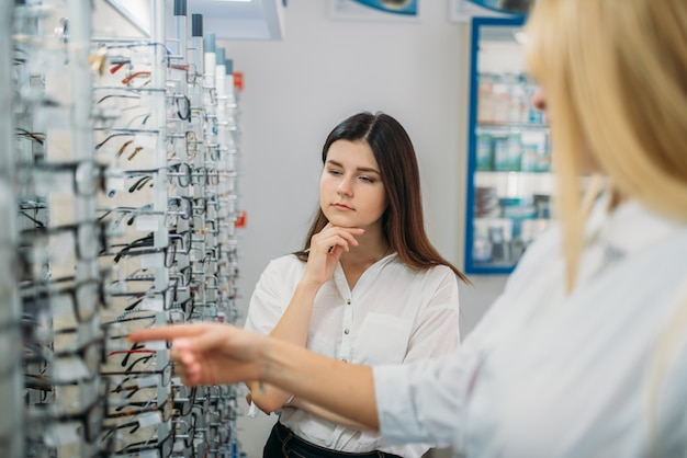 Female optician and buyer against showcase with glasses in optics store. selection of eyeglasses with professional optometrist.