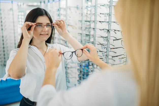 Female optician and buyer chooses glasses frame against showcase with eyeglasses in optics store. selection of spectacles with professional optometrist