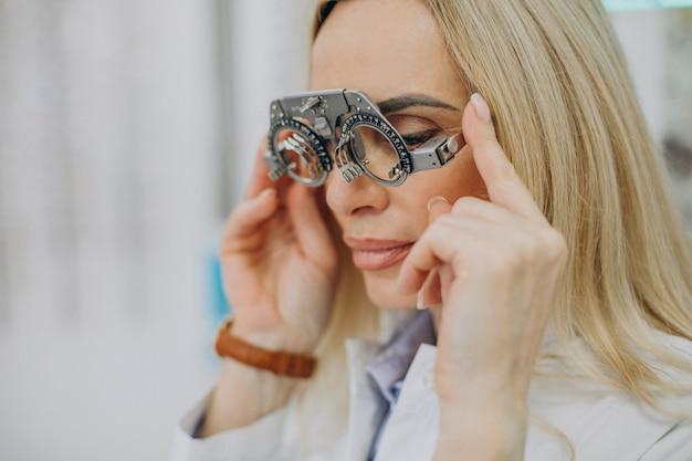 彼女の視力を測定する女性の眼鏡技師