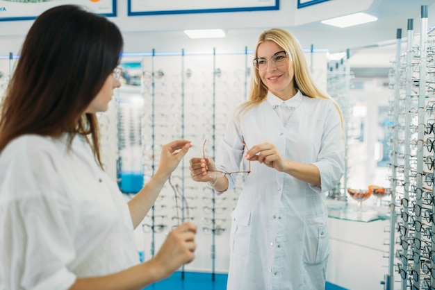Female optician shows glasses to buyer in optics store. selection of eyeglasses with professional optometrist