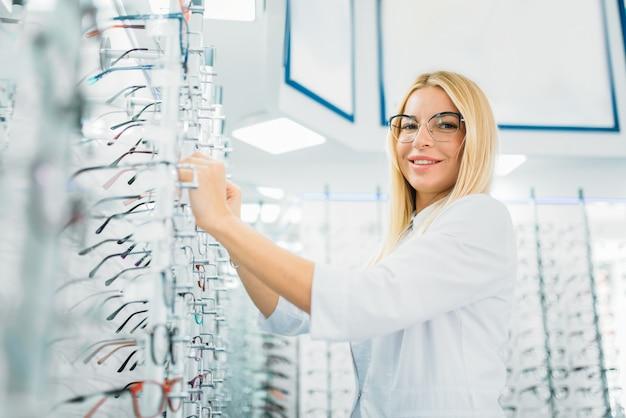女性の眼鏡技師は眼鏡店で眼鏡を示しています