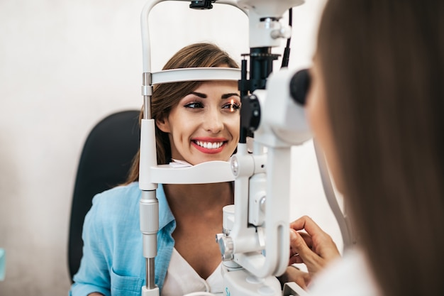Женский оптометрист проверяет зрение пациента в офтальмологической клинике. здравоохранение и медицинская концепция.