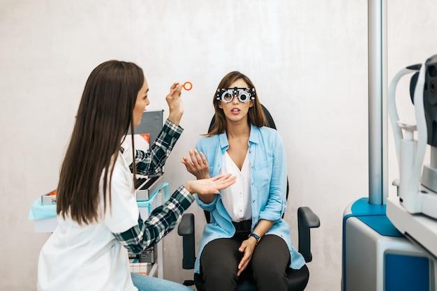 안과에서 환자의 시력을 검사하는 여성 검안사. 의료 및 의료 개념입니다.