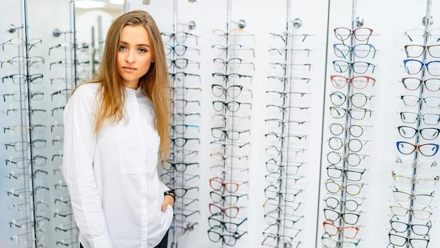 女性の検眼医である眼鏡技師は、光学店でたくさんの眼鏡をかけて立っています。