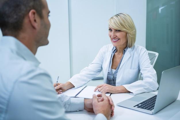 Женский окулист разговаривает с пациентом мужского пола