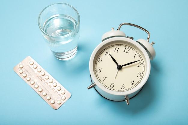 女性の経口避妊薬、コップ一杯の水、青色の目覚まし時計。