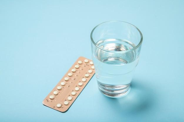 Женские оральные контрацептивы и стакан воды на синем