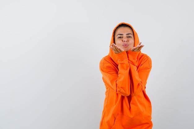Donna in felpa con cappuccio arancione che soffia aria bacio con labbra imbronciate e sembra carina