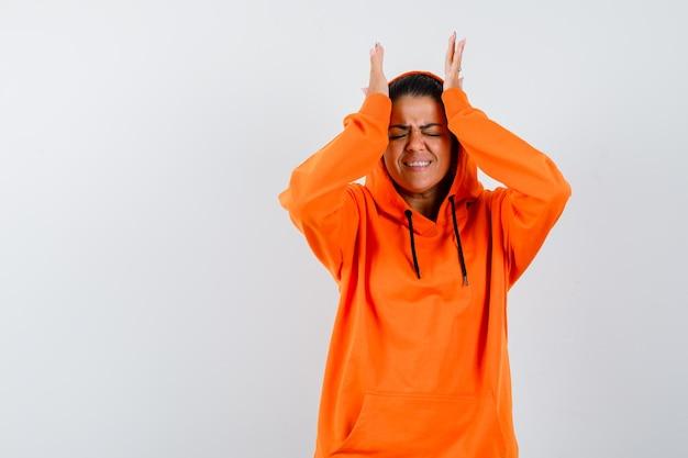 Donna in felpa con cappuccio arancione che si tiene per mano sulla testa e sembra dispiaciuta