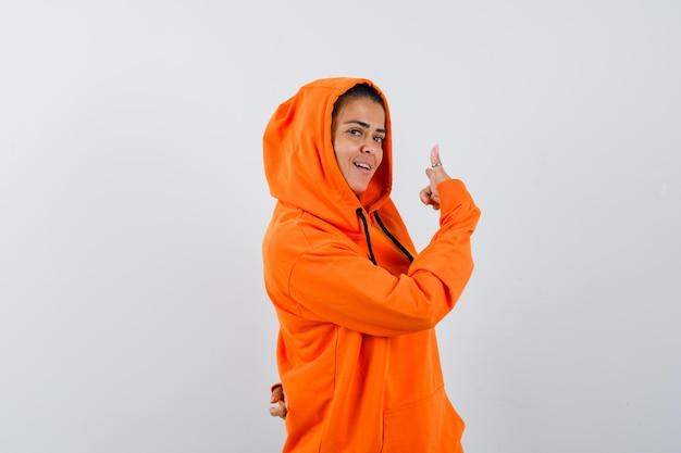 Donna in felpa con cappuccio arancione che punta indietro e sembra allegra