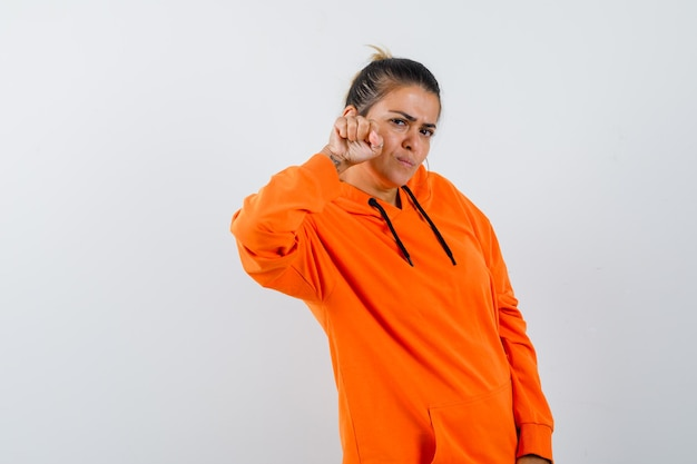 Donna in felpa con cappuccio arancione in piedi in posa da combattimento e sembra potente