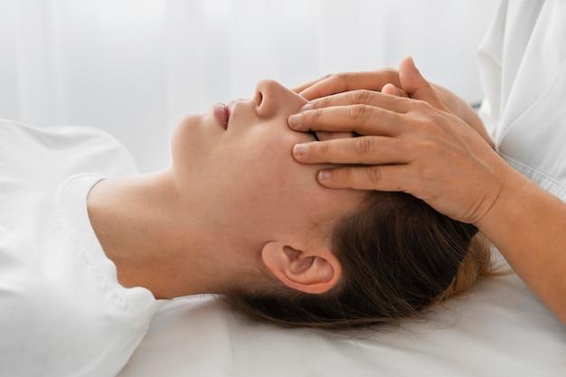 Женщина-остеопат лечит пациента, массируя ее лицо
