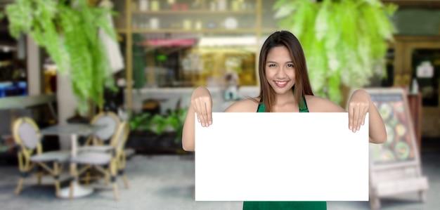 テラスでホワイトボードを示す女性の所有者