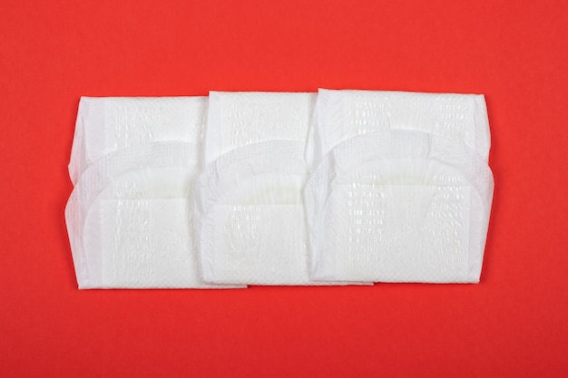 Female pad on red background, symbol of menstruation in women.